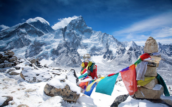 The colorful flags on top of the mountain Kala Pattar. Behind the prayer flags can be seen Mount Everest and Nuptse. Photo is taken in the Himalayas
